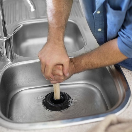 Plumber Unclogging Kitchen Sink